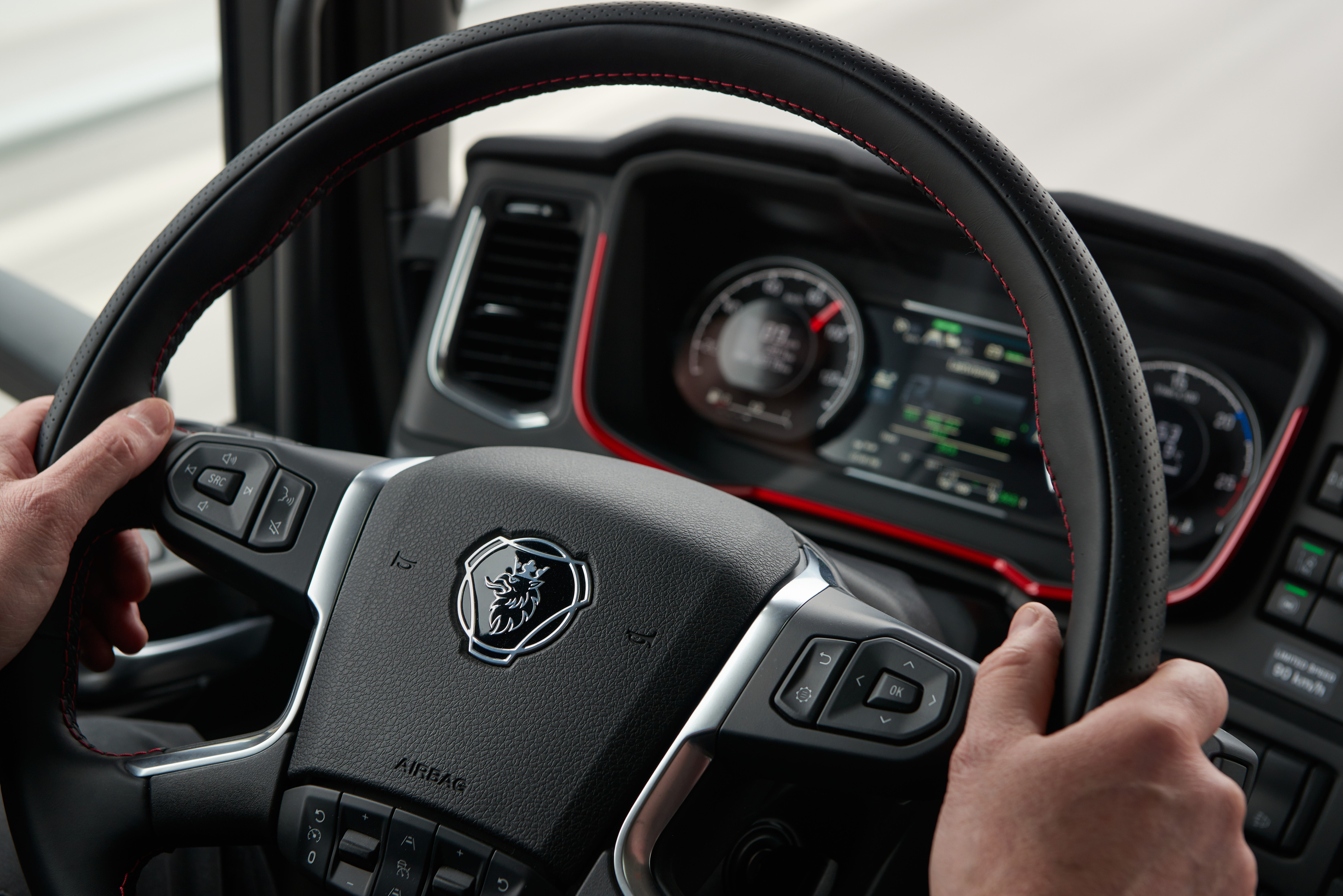 Driver holding Scania steering wheel
